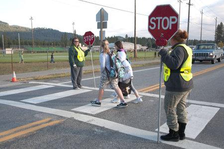 crosswalk: Rathdrum, Idaho. October 4, 2010. Unidentified crossing guard  stops traffic for kids crossing the street in Rathdrum Idaho on October 4, 2010.
