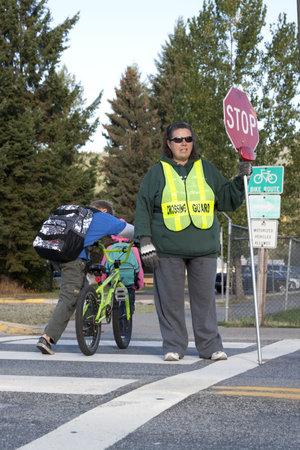 Rathdrum, Idaho. 4 Ottobre 2010. Guardia di attraversamento non identificato smette di traffico per i ragazzi che attraversano la strada in Rathdrum Idaho il 4 ottobre 2010. Archivio Fotografico - 7959692
