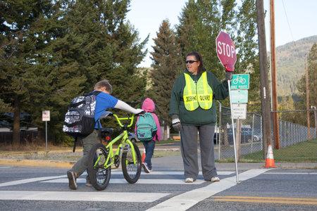 Rathdrum, Idaho. 4 Ottobre 2010. Guardia di attraversamento non identificato smette di traffico per i ragazzi che attraversano la strada in Idaho Rathdrum, 4 ottobre 2010. Archivio Fotografico - 7959693