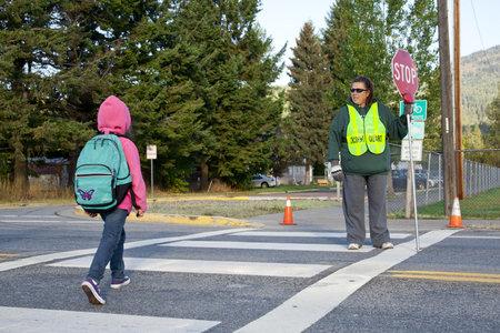 senda peatonal: Rathdrum, Idaho. 4 De octubre de 2010. Guardia de cruce no identificados detiene el tr�fico para ni�os que cruzar la calle en Idaho de Rathdrum el 4 de octubre de 2010.