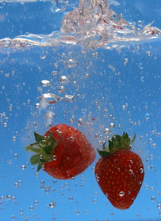 Two strawberries dropped in some bubbly tonic water.