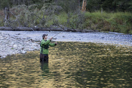A fly fisherman on the river catching fish.