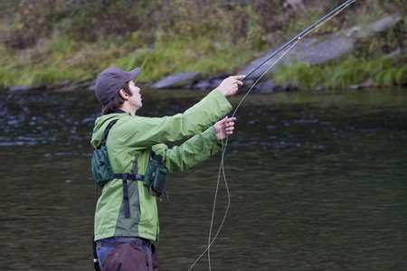 A fly fisherman on the river catching fish. Stock Photo - 8151713