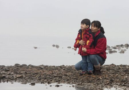 A mother and her little son are on a rocky shoreline by a lake. photo