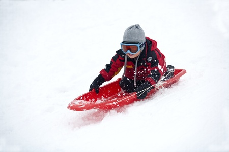 sled: A young boy shows his excitement sledding down a hill in winter. Stock Photo
