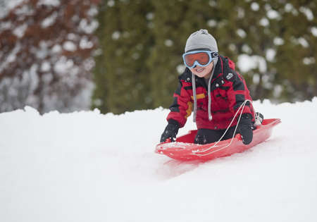 A young boy shows his excitement sledding down a hill in winter. Stok Fotoğraf