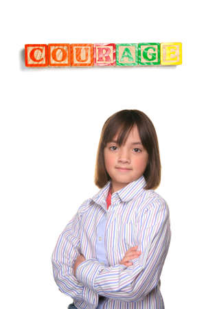 A young student showing couragous pose under word blocks. Stock Photo