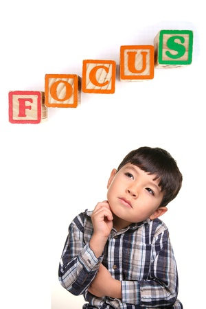 xyz: A concept image of a young boy under the word blocks that says focus.
