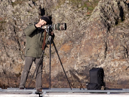 Photographer checks his camera gear while photographing by Coeur d'Alene lake in northern Idaho on December 17, 2010 Stock Photo - 8477424
