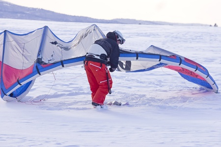 kiting: A man adjusts his snow kite before kiting on his snowboard.