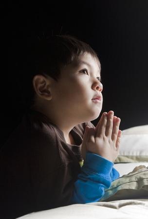 Un joven dice sus oraciones justo antes de su hora de acostarse. Foto de archivo - 8681705