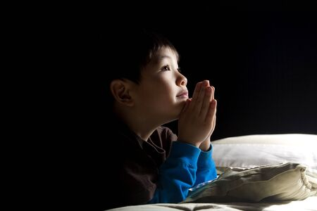 A young boy says his prayers just before his bedtime. photo