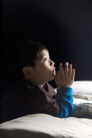 mano de dios: Un joven dice sus oraciones justo antes de su hora de acostarse.