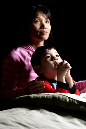 A woman says prayers with her son at bedtime.