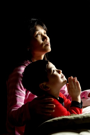 ni�o orando: Una mujer dice oraciones con su hijo antes de dormir.