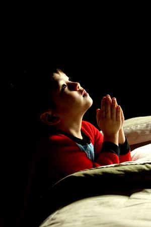 ni�o orando: Un joven dice sus oraciones justo antes de su hora de acostarse.