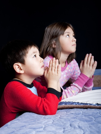 A brother and sister say their prayers just before bedtime. Stok Fotoğraf