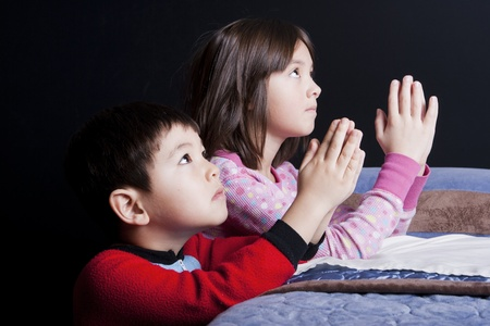 A brother and sister say their prayers just before bedtime. Stock Photo