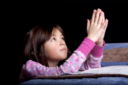 A young girl says her prayers just before bed time.