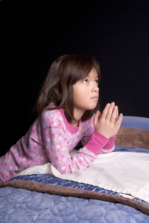 just in time: A young girl says her prayers just before bed time.