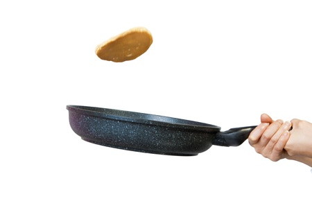 flip: The process of flipping a pancake in a frying pan against a white background. Stock Photo