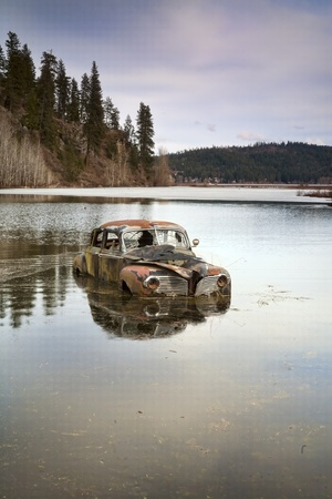 An old antique car sits swamped in a flooded pond.