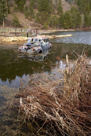 swamped: An old antique car sits swamped in a flooded pond.