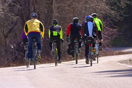 A rear view of several bicyclists on a country road. photo