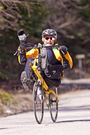 04122011-Hauser Lake, Idaho. An older man on a recumbent bike waves in Hauser Lake, Idaho.