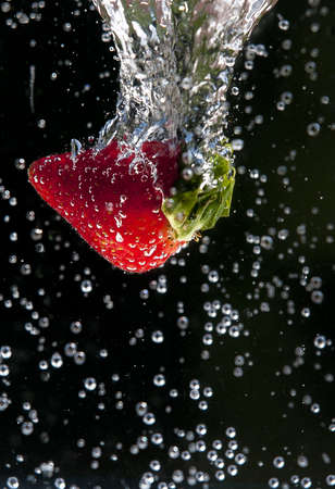 Motion of strawberry in water. photo