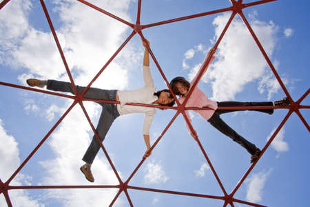 Mother and her daughter up high on the piece of playground equipment. photo