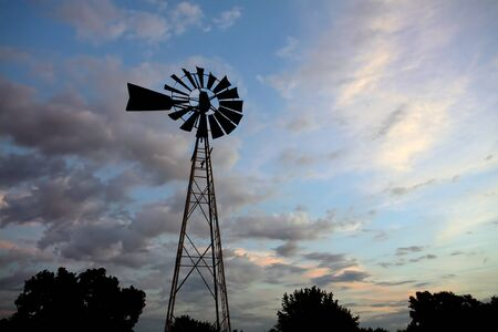 An old windmill in silhouette set against the setting sun. Banco de Imagens