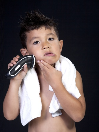 A young boy has fun pretending to shave with an electric razor. 写真素材