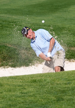 Rathdrum, Idaho USA, August, 21, 2011. Lakeland H.S. boosters event. A man hits the ball out of a sand trap at the Links golf course near Rathdrum, Idaho. Stock Photo - 10581392