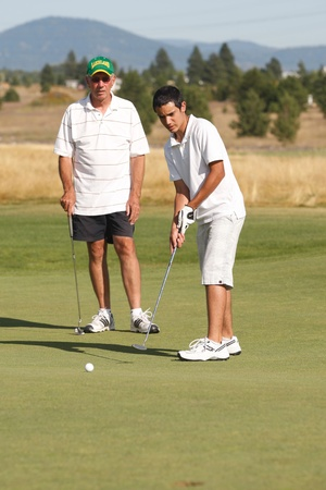 Rathdrum, Idaho USA, August, 21, 2011. Lakeland H.S. boosters event. A teen golfer putts the ball while dad watches.
