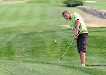 A young man makes a chip shot onto the green at the Links golf course near Rathdrum, Idaho. Stock Photo - 10581391