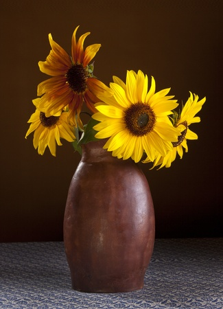 vase: Arrangement of sunflowers in a clay vase. Stock Photo