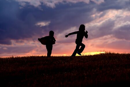 A brother and sister run and play at sunset. Stock Photo - 10741238