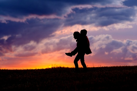 A young girl carries her brother on her back at sunset.