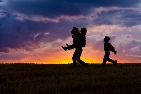 silueta niño: Una mujer lleva a su hija sobre su espalda mientras su hijo camina detrás de la puesta del sol.