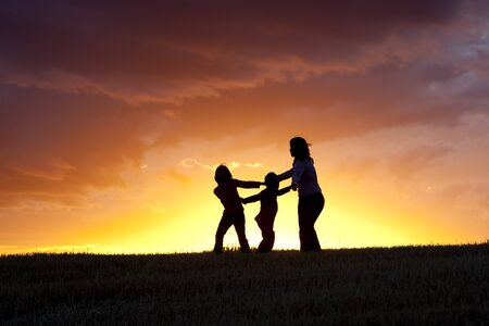 A mother and her two kids play ring around the rosie at sunset. Stock Photo - 10741253