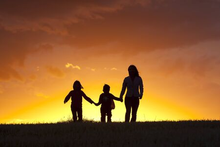 A mother and her two kids walk along into the sunset. photo