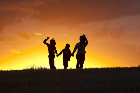 A mother, daughter, and son skip along at sunset. photo