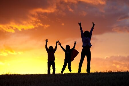 A woman and her two kids jump for joy at sunset. Stock Photo - 10741291