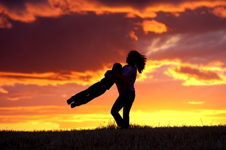 A mother plays with her son by swinging him in the air. Stock Photo - 10741230