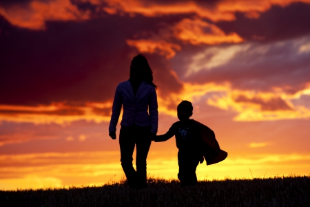 A tender moment of a mom and her son walking along at sunset.