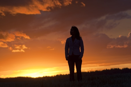 A woman silhouetted by the back light of the sunset stands alone in a field.