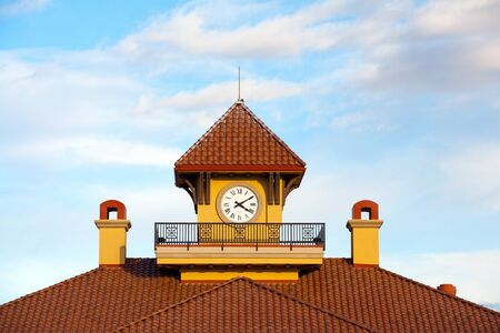 imbedded: The top part of a tiled roof with a clock imbedded in it  Stock Photo