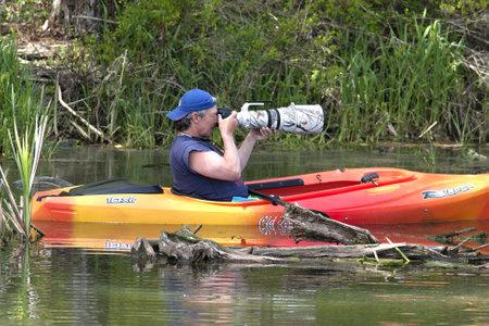 Fernan Lake, Idaho - May 8, 2012  A man feels safe enough in his kayak to photograph birds with a big lens on Fernan Lake, Idaho on May 8th 2012