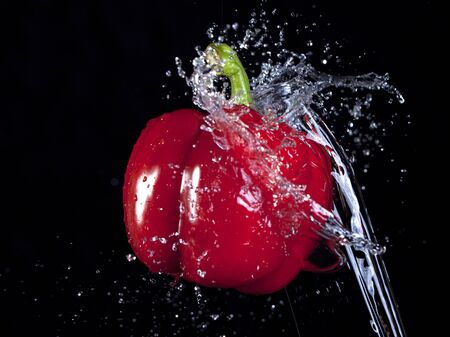 Water is being splashed on a red bell pepper in the air
